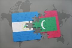 desconcierte con la bandera nacional de Nicaragua y de Maldivas en un mapa del mundo Imágenes de archivo libres de regalías