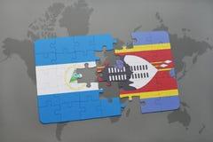 desconcierte con la bandera nacional de Nicaragua y de Swazilandia en un mapa del mundo Fotografía de archivo