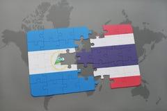 desconcierte con la bandera nacional de Nicaragua y de Tailandia en un mapa del mundo Imagen de archivo