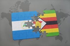 desconcierte con la bandera nacional de Nicaragua y de Zimbabwe en un mapa del mundo Foto de archivo libre de regalías