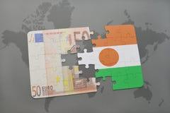 desconcierte con la bandera nacional de Niger y del billete de banco euro en un fondo del mapa del mundo Imagen de archivo libre de regalías