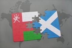 desconcierte con la bandera nacional de Omán y de Escocia en un fondo del mapa del mundo Fotografía de archivo
