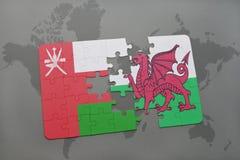 desconcierte con la bandera nacional de Omán y de País de Gales en un fondo del mapa del mundo Foto de archivo