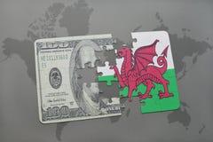 desconcierte con la bandera nacional de País de Gales y del billete de banco del dólar en un fondo del mapa del mundo Imagenes de archivo
