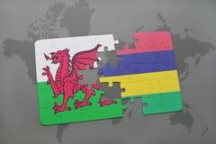 desconcierte con la bandera nacional de País de Gales y de Mauricio en un mapa del mundo Foto de archivo