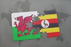 desconcierte con la bandera nacional de País de Gales y de Uganda en un mapa del mundo Imagen de archivo libre de regalías