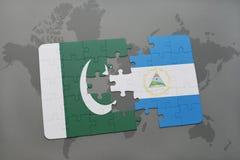 desconcierte con la bandera nacional de Paquistán y de Nicaragua en un fondo del mapa del mundo Fotografía de archivo