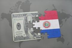 desconcierte con la bandera nacional de Paraguay y del billete de banco del dólar en un fondo del mapa del mundo Imágenes de archivo libres de regalías