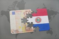 desconcierte con la bandera nacional de Paraguay y del billete de banco euro en un fondo del mapa del mundo Foto de archivo libre de regalías