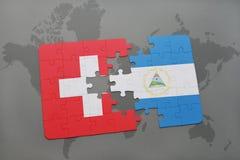 desconcierte con la bandera nacional de Suiza y de Nicaragua en un fondo del mapa del mundo Imagen de archivo