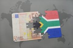 desconcierte con la bandera nacional de Suráfrica y del billete de banco euro en un fondo del mapa del mundo Foto de archivo libre de regalías