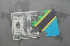 desconcierte con la bandera nacional de Tanzania y del billete de banco del dólar en un fondo del mapa del mundo Fotos de archivo libres de regalías