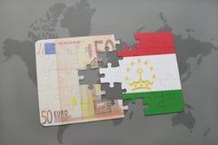 desconcierte con la bandera nacional de Tayikistán y del billete de banco euro en un fondo del mapa del mundo Imagen de archivo