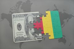 desconcierte con la bandera nacional del billete de banco de Guinea y del dólar en un fondo del mapa del mundo Imágenes de archivo libres de regalías