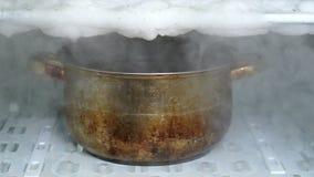 Descongelando un refrigerador usando el cazo grande de la cocina por completo de la agua caliente almacen de video