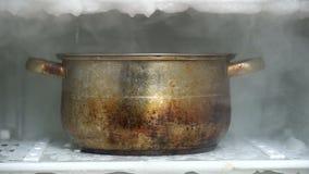 Descongelando un refrigerador usando el cazo grande de la cocina por completo de la agua caliente metrajes