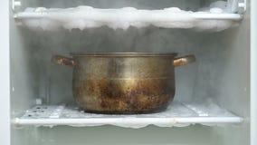 Descongelando un refrigerador usando el cazo grande de la cocina por completo de la agua caliente almacen de metraje de vídeo