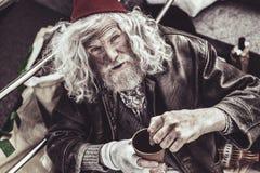 Desconhecido mostrando mendicantes idosos onde pôr o dinheiro fotografia de stock