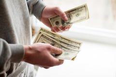 Desconte dentro as m?os Lucros, economias Pilha de d?lares Homem que conta o dinheiro Dólares nas mãos do homem Sucesso, motivaçã fotografia de stock