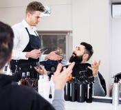Descontento de la sensación del cliente sobre su nuevo corte de pelo en el salón de pelo Fotos de archivo libres de regalías