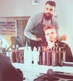Descontento de la sensación del cliente sobre su nuevo corte de pelo en el salón de pelo Foto de archivo libre de regalías