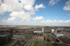 Descripción granangular en 100 metros de altura sobre el horizonte de Rotterdam con el cielo azul y las nubes de lluvia blancas Imagenes de archivo