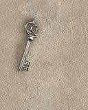 Descubra a chave de bronze velha do tesouro dentro da areia suja, rendição 3D Imagem de Stock Royalty Free