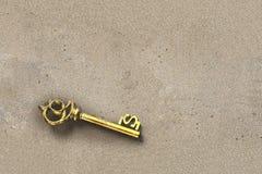 Descubra la llave del tesoro del oro en forma del dólar dentro del nob sucio de la arena Imagen de archivo libre de regalías