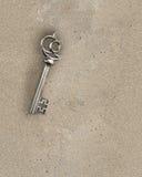 Descubra la vieja llave de bronce del tesoro dentro de la arena sucia, representación 3D Imagen de archivo libre de regalías