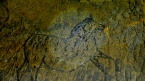 Descubrimiento de la pintura prehistórica del caballo en cueva de la piedra arenisca El proyector brilla en la pintura humana his almacen de video