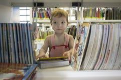 Descubrimiento de los libros en mi primera biblioteca Imagenes de archivo