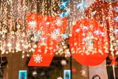 Descuento grande de la venta el 70%, una bandera sobre el vidrio con la reflexión de las guirnaldas del ` s del Año Nuevo Fotografía de archivo