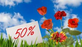 Descuento para la venta, descuento del 50 por ciento, flores hermosas en el primer de la hierba imágenes de archivo libres de regalías
