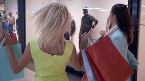 Descuentos estacionales, precipitación joven del shopaholics de las novias a la venta en tiendas en la alameda de compras durante metrajes