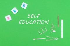 Desde arriba de fuentes de escuela de los minitures y de las letras de madera de ABC en fondo verde con la educación del uno mism Imagen de archivo libre de regalías