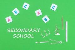 Desde arriba de fuentes de escuela de los minitures y de las letras de madera de ABC en fondo verde con la escuela secundaria del Fotografía de archivo libre de regalías