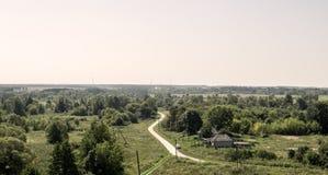 Desde arriba de la colina que pasa por alto el pueblo viejo y el camino que se van en la distancia imagen de archivo