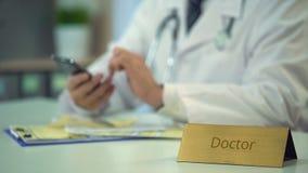 Desdobramento masculino do doutor e zumbir no smartphone, serviço em linha da consulta vídeos de arquivo