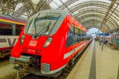 DESDREN, DEUTSCHLAND - MARZO 23, 2016: Der moderne rote HB-Zug, der Passagiere, Abfahrt des Zugs waitting ist, kommt Stockfoto