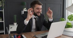 Desear al hombre de negocios que recibe buenas noticias en el ordenador portátil almacen de metraje de vídeo