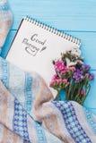 Desee la buena mañana en las flores de la página y del statice del cuaderno fotografía de archivo