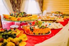 Desee la comida fría servida de la fruta en la tabla lujosa del partido en restaurante Foto de archivo libre de regalías