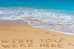 DESEE que USTED ESTUVIERA AQUÍ insctiption en la arena mojada de la playa con el turquo imagen de archivo
