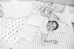 Desee su buena mañana Niño de la muchacha puesto en cama su dormitorio Niño despierto y lleno de energía El tiempo agradable rela imagen de archivo libre de regalías