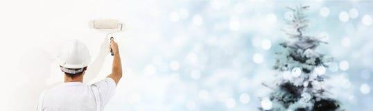 Desee un concepto de la Feliz Navidad, pintor con el rodillo que pinta el A.C. imagen de archivo libre de regalías