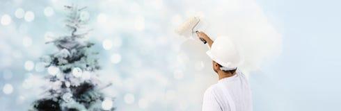 Desee un concepto de la Feliz Navidad, pintor con el rodillo que pinta el A.C. foto de archivo