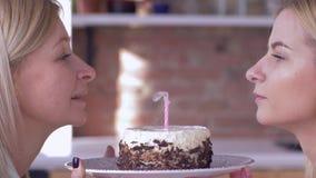 Desejo do aniversário, mamã de sorriso com velas de sopro da filha adulta no bolo do feriado e sorrisos e para olhar se