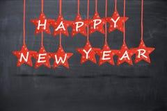 Desejo do ano novo feliz com as estrelas vermelhas isoladas no fundo do quadro-negro Fotos de Stock Royalty Free