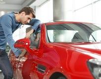 Desejo era meu carro. Homens novos consideráveis que estão perto do sp vermelho Imagens de Stock
