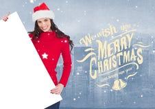Desejos e mulher do Feliz Natal no chapéu de Santa que guarda um cartaz vazio Fotos de Stock Royalty Free